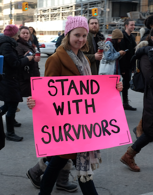 Photo of a woman with a placard: Stand with survivors